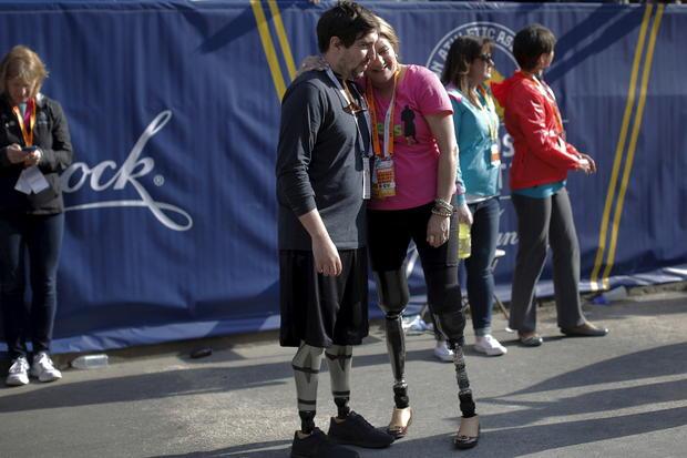 Boston Marathon bombing survivors Jeff Bauman and Celeste Corcoran embrace at the finish line of the 120th running of the Boston Marathon in Boston, Massachusetts